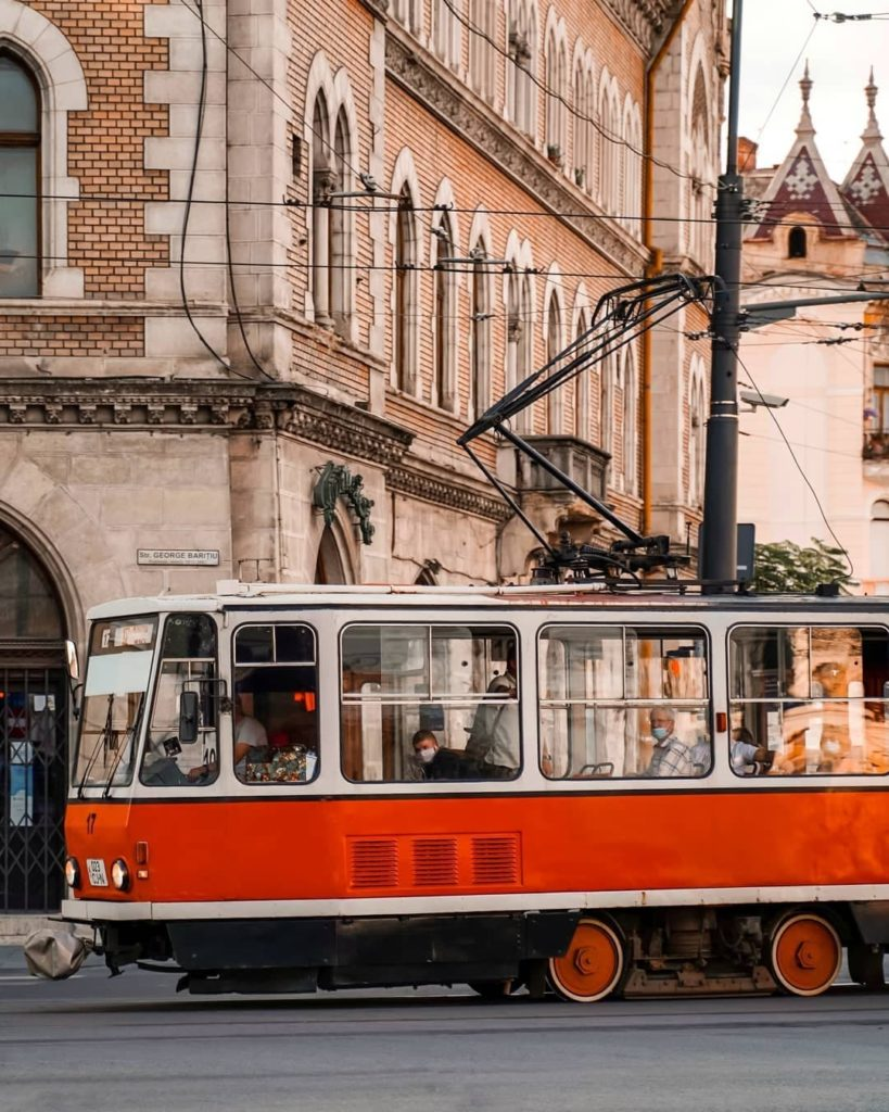 Red trolley going through the streets of Cluj Napoca with masked passengers on board.