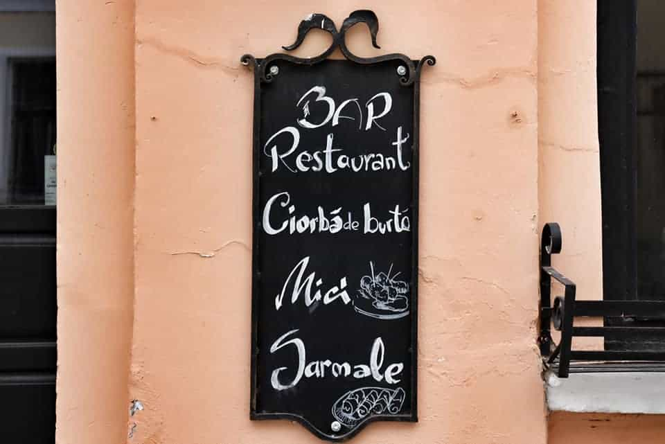 Chalkboard sign on a Romanian restaurant with the daily specials, hung on a pale pink concrete building.