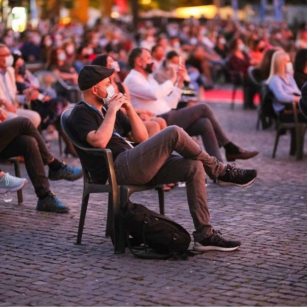 Socially-distanced people sitting on lawn chairs with masks on during the Film Festival in Cluj Napoca, Romania