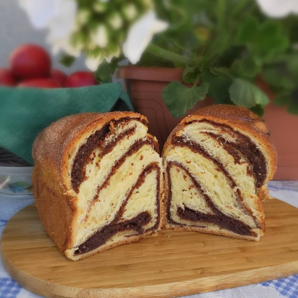 Loaf of cozonac cut in half and facing the camera with the inside shwoing.  Blurred fruits and plants in the background.