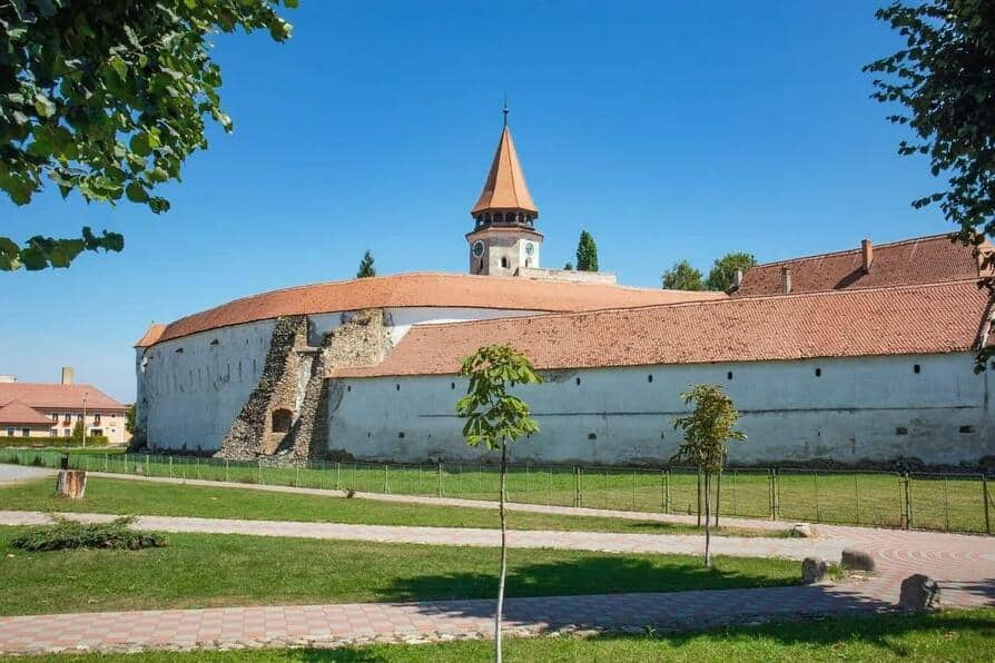 Fortified church in Romania with red roofs and blue skies during spring.