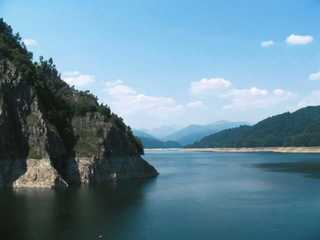 Still lake in Brasov, perfect for paddle boarding aside the mountains.