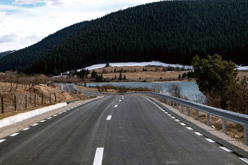 Road in Transylvania approaching a small lake with forested mountains in the background.