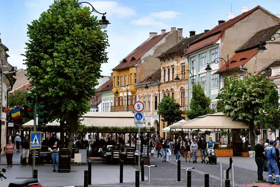 Outdoor terraces and trees line the colorful street of Nicolae Balcescu in Sibiu, Romania