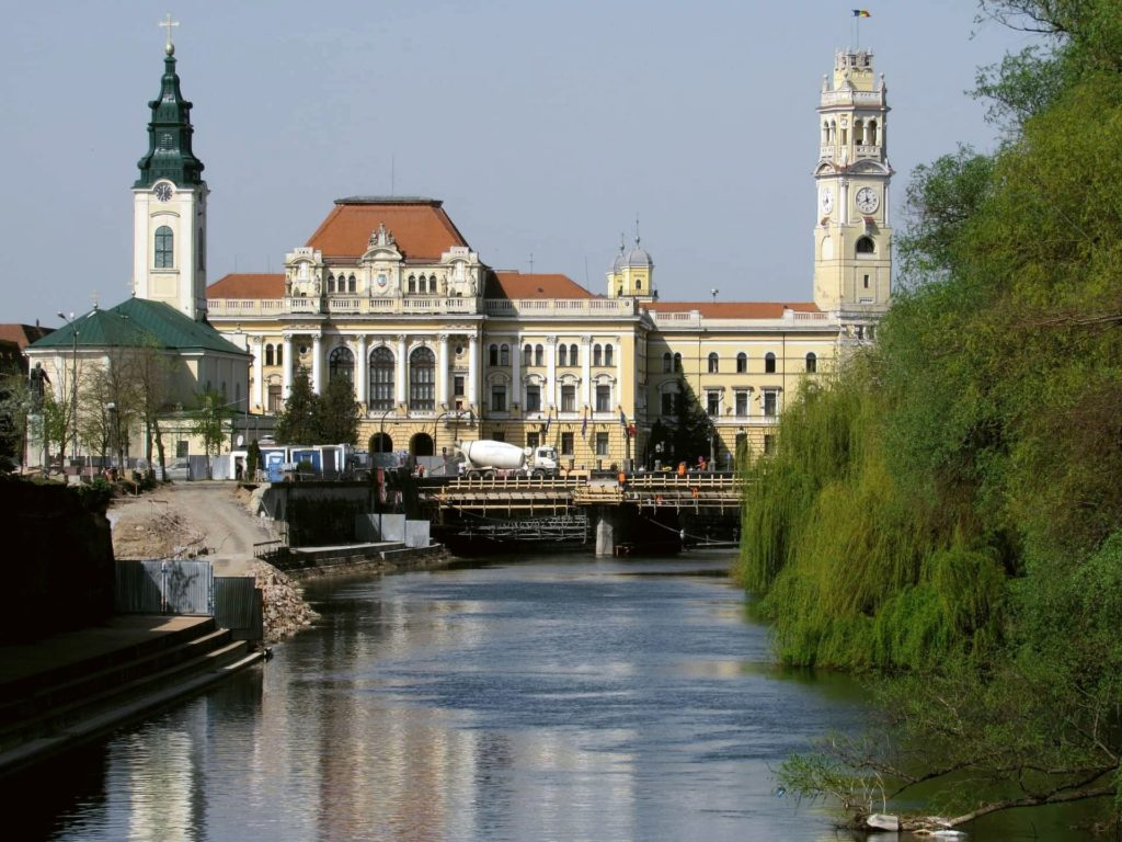 View of Oradea along the river with gorgeous architecture and riverside greenery.