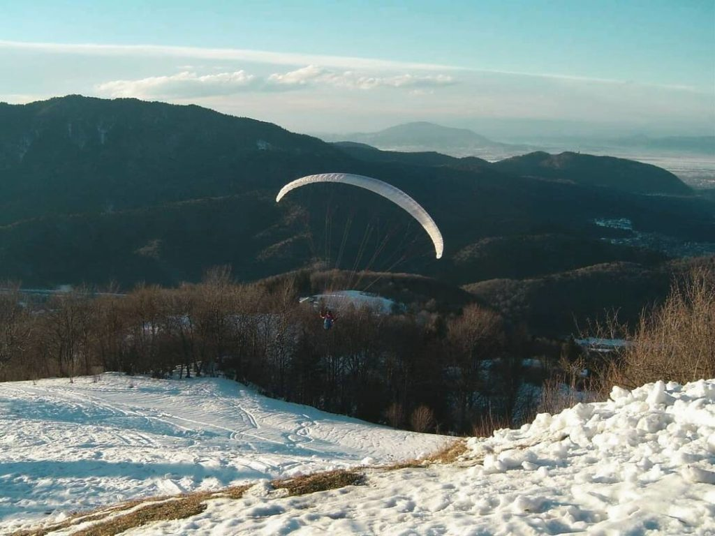 Paraglider over snow-covered mountains on a day trip from Brasov.