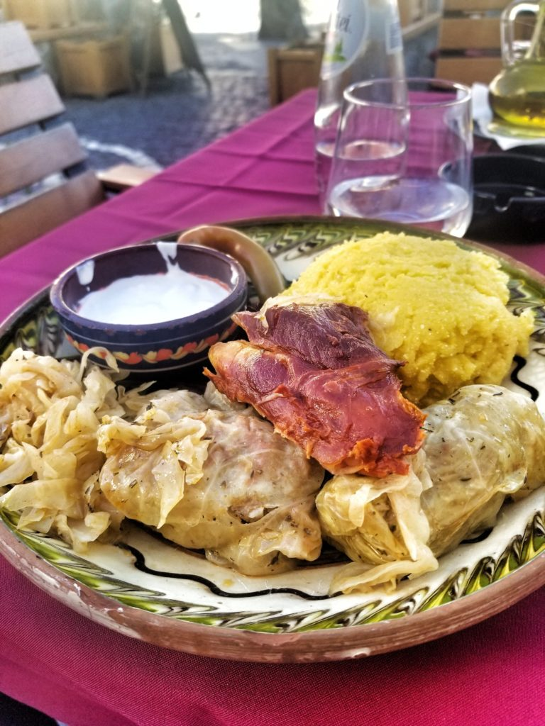 Plate of sarmale with polenta and pork, outside dining in Sibiu, Romania.