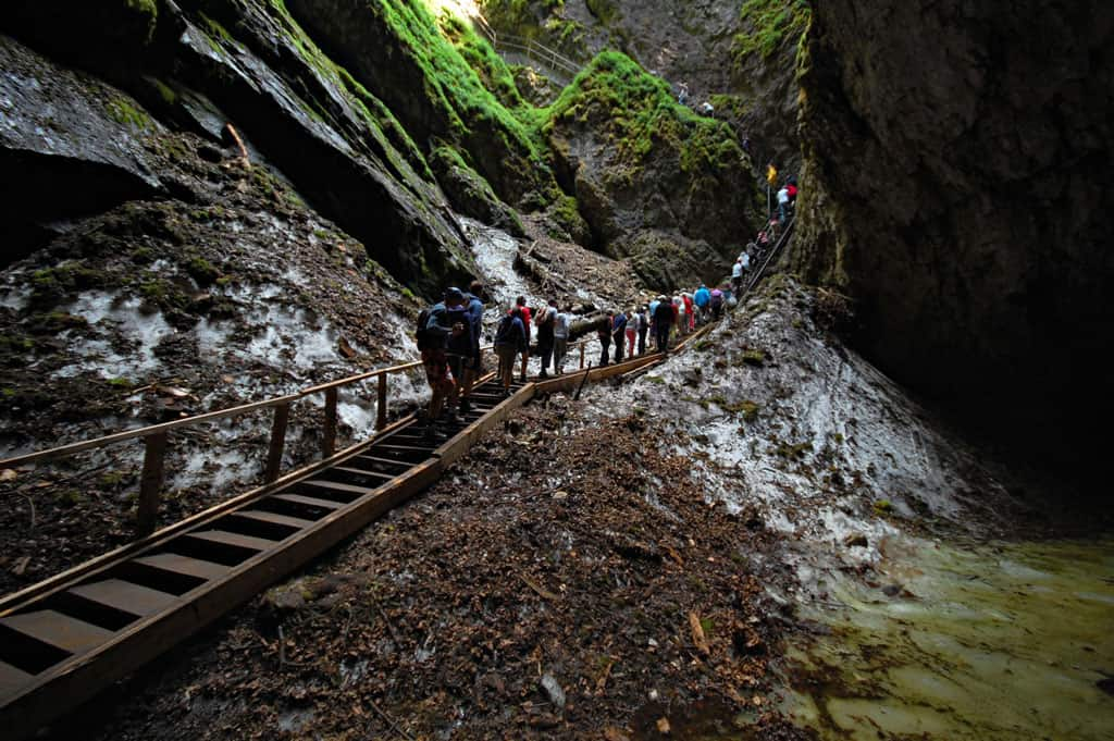 Line of people trekking through Scarisoara glacier cave, a great day trip from Cluj Napoca.