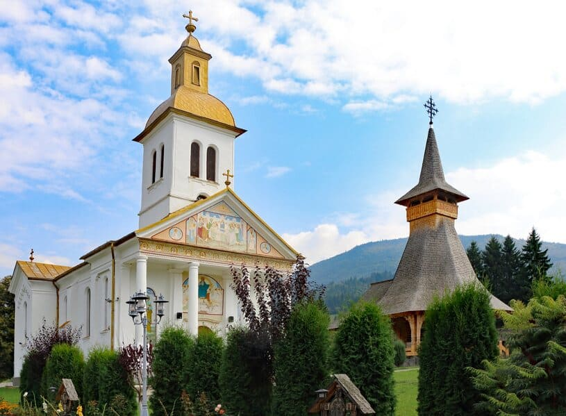 Two wooden churches in Maramures, with mountains in the background and green, lush bushes in the foreground under blue and white skies.