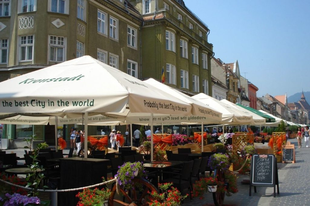 Strada Republicii in Brasov, with restaurant tables, red flowers, and shaded umbrellas lining the street.