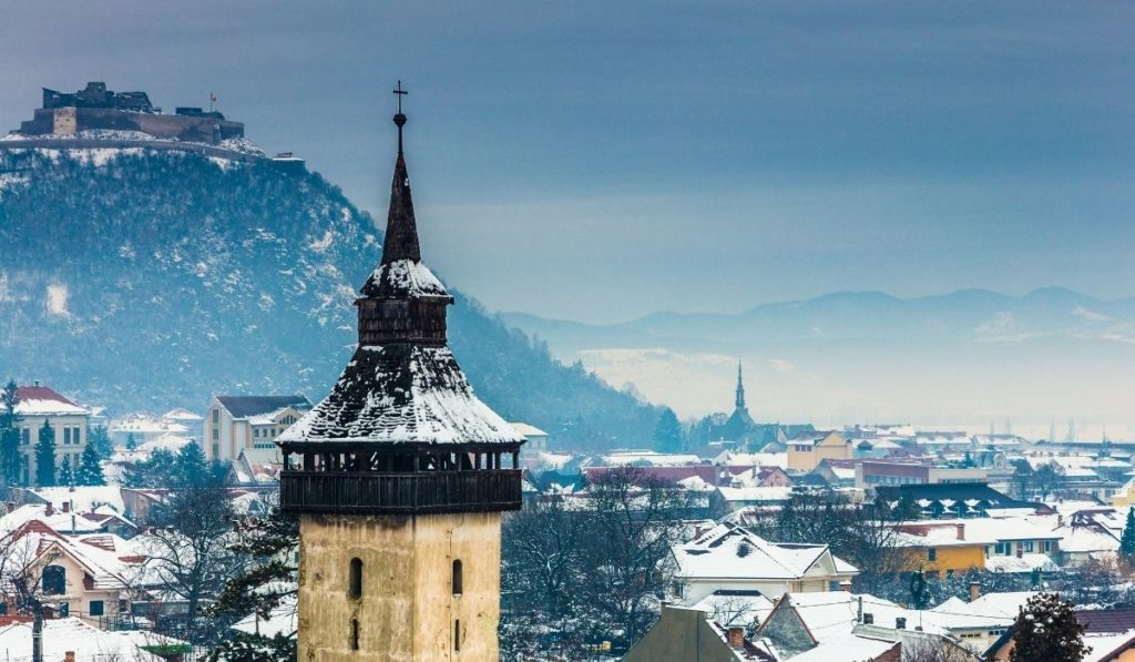 Transylvanian town under a blanket of snow with large black spire in the foreground and a fortress on a hill in the background.