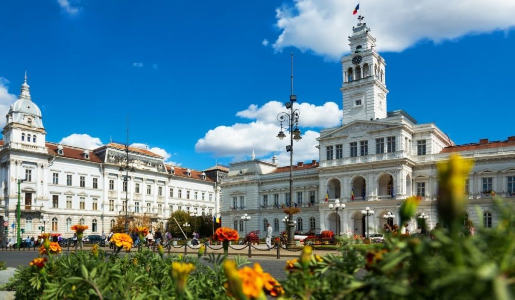 Arad Town Hall with colorful flowers in the foreground under bright blue skies.