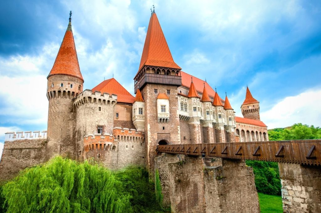 Red pointed roofs of  Corvin Castle with a bridge leading up to the entrance under blue and cloudy skies.