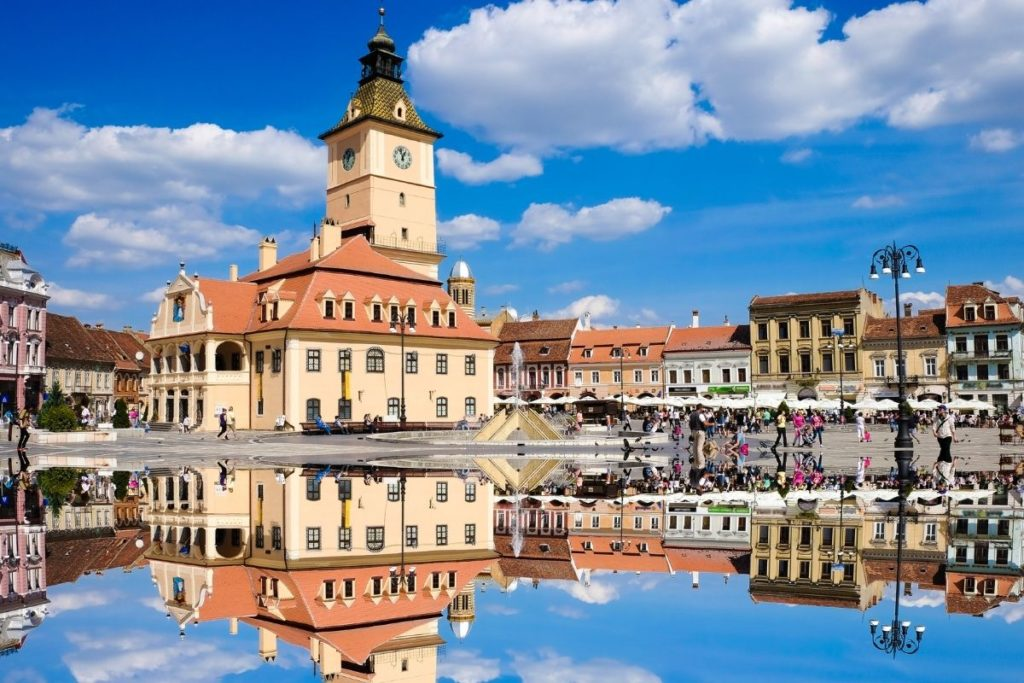 Piata Sfatului in Brasov, with the surrounding buildings reflected in a large puddle in the square.