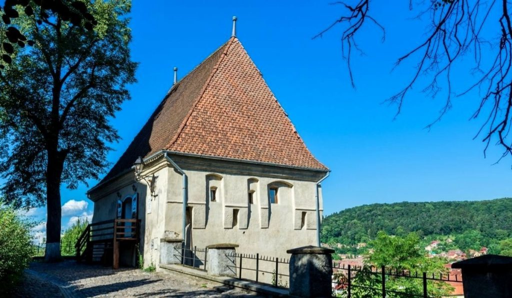 Ironsmiths' Tower in Sighisoara, Romaia with a red pyramid roof and creamy white façade.