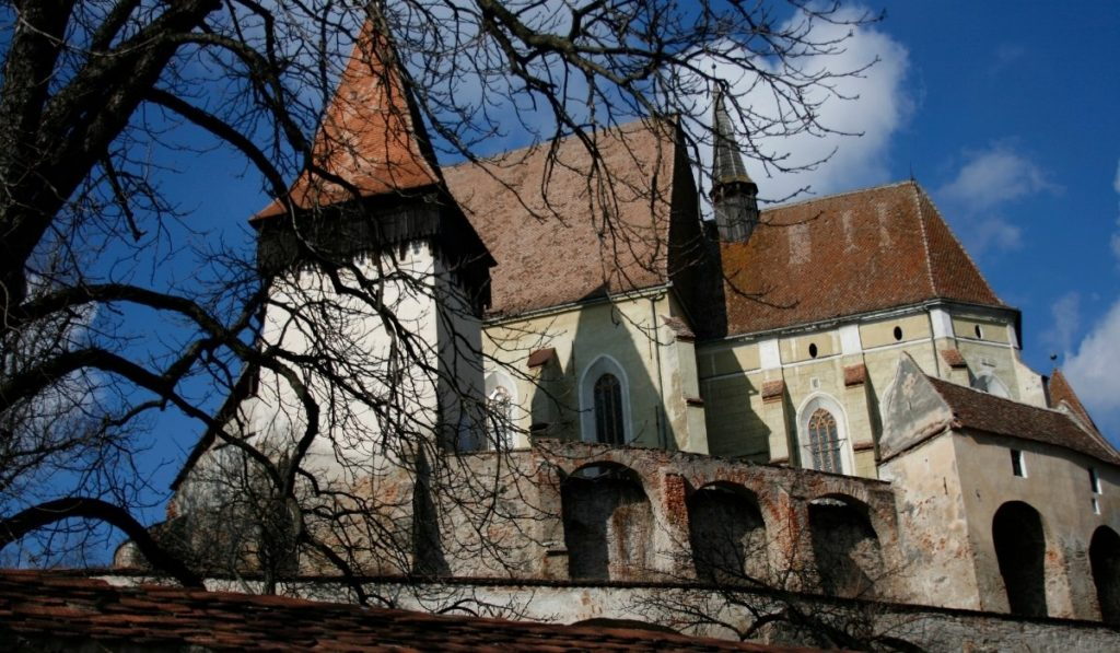 Biertan Fortified Church, one of the best things to do in Transylvania, with leave-less trees in the foreground and blue skies.