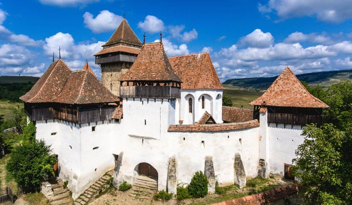 One of the most famous of all the Transylvanian fortified churches, the fortified church of Viscri is white with red tiled roof.