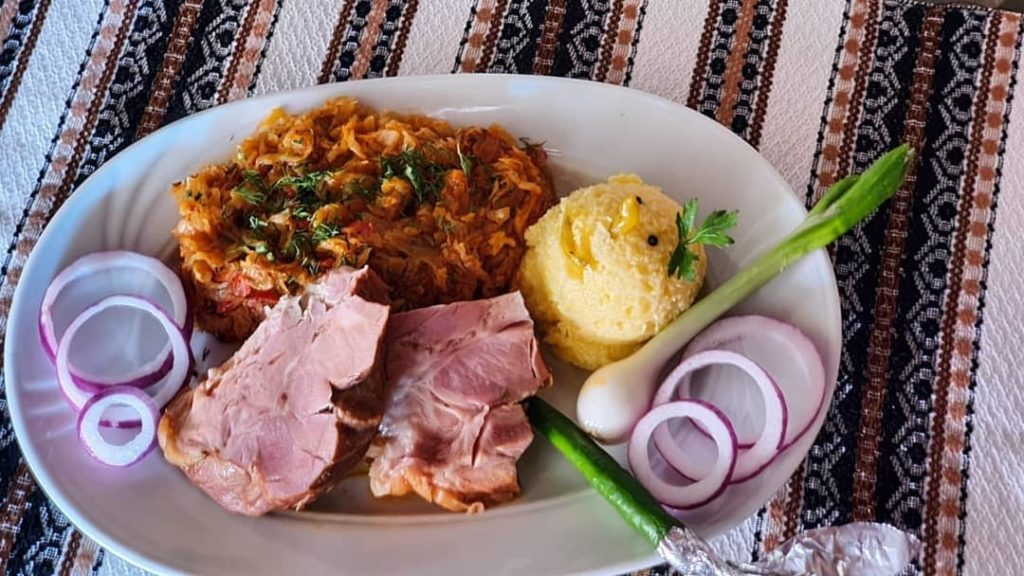 Ciolan cu varza, a traditional Banat dish made with pork, cabbage, and polenta with some fresh veggies.